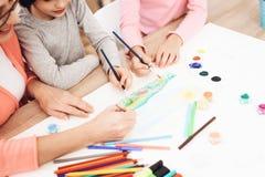 Schöne ältere Frau unterrichtet Kinder zu zeichnen Kleine Kinderabgehobener betrag Zeichnungslektionen stockfoto