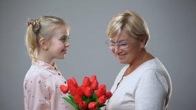 Schöne ältere Geschenk von der Enkelin nehmende und umarmende Dame Blumen, Liebe stock video footage