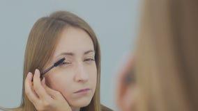 Schöne Öffnung der jungen Frau und sich setzen Wimperntusche stock video footage