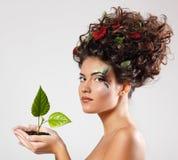 Schöne Ökologie des jugendlich Mädchens mit grünem Baumtrieb lizenzfreie stockfotografie