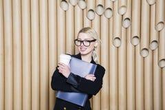 Schöne überraschte blonde Geschäftsfrau im schwarzen Kleid und in den Gläsern mit Kaffeetasse Lizenzfreie Stockfotografie