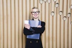 Schöne überraschte blonde Geschäftsfrau im schwarzen Kleid und in den Gläsern mit Kaffeetasse Lizenzfreies Stockfoto