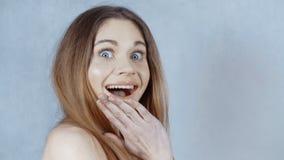 Schöne überraschte lächelnde Frau mit offenem Mund über grauem Hintergrund stock footage