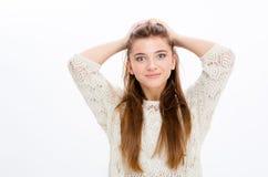 Schöne überzeugte junge Frau, die ihr Haar durch Hände hält Stockfotos