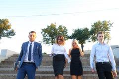 Schöne überzeugte Leute, zwei Jungen und zwei Mädchen, lächelnd, hol Lizenzfreie Stockfotografie