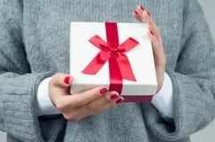 Schöne Abbildung Frau in gestrickter Strickjacke hält Weihnachtsgeschenk Lizenzfreie Stockbilder