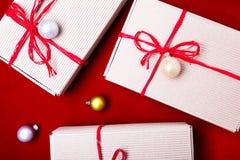 Schöne Abbildung Weihnachtsgeschenke in den Handwerkskästen und rotes Band auf rotem Hintergrund Flache Lage mit Kopienraum flach Lizenzfreie Stockbilder