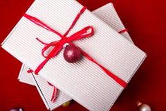Schöne Abbildung Weihnachtsgeschenke in den Handwerkskästen und rotes Band auf rotem Hintergrund Flache Lage mit Kopienraum flach Lizenzfreie Stockfotos