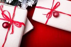 Schöne Abbildung Weihnachtsgeschenke in den Handwerkskästen und rotes Band auf rotem Hintergrund Flache Lage mit Kopienraum flach Stockfotografie