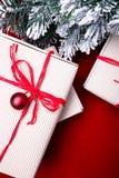 Schöne Abbildung Weihnachtsgeschenke in den Handwerkskästen und rotes Band auf rotem Hintergrund Flache Lage mit Kopienraum flach Stockfoto