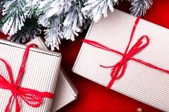 Schöne Abbildung Weihnachtsgeschenke in den Handwerkskästen und rotes Band auf rotem Hintergrund Flache Lage mit Kopienraum flach Stockbilder