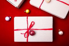 Schöne Abbildung Weihnachtsgeschenke in den Handwerkskästen und rotes Band auf rotem Hintergrund Flache Lage mit Kopienraum flach Lizenzfreie Stockfotografie