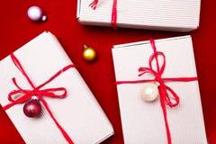 Schöne Abbildung Weihnachtsgeschenke in den Handwerkskästen und rotes Band auf rotem Hintergrund Flache Lage mit Kopienraum flach Stockbild