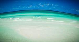 Schöne abstrakte Ansicht des tropischen Strandes mit steigendem gebogenem Ozean und dunkelblauem Himmelhintergrund Lizenzfreie Stockfotos