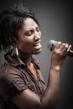 Schöne Afrikanerin, die mit dem Mikrofon singt Lizenzfreie Stockfotos