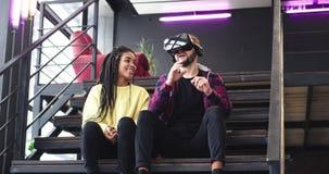 Schöne afrikanische Dame und charismatischer Kerl, die mit Gläsern einer virtuellen Realität spielt und zusammen die Zeit in a ge stock video footage