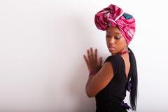 Schöne afrikanische Frau, die ein traditionelles Kopftuch trägt Stockfotos