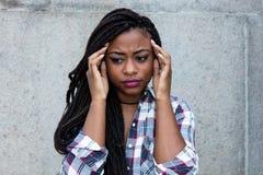 Schöne afrikanische Frau mit schmerzlichen Kopfschmerzen lizenzfreies stockfoto