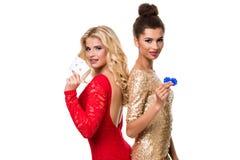 Schöne afrikanische Frau und kaukasische junge Frau mit dem langen hellen blonden Haar in der Abendausstattung Halten von Spielka Lizenzfreie Stockbilder