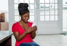 Schöne Afroamerikanerfrau, die Mitteilung mit Telefon sendet stockbild