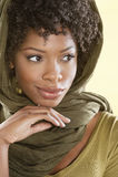 Schöne Afroamerikanerfrau, die weg über farbigem Hintergrund schaut Lizenzfreie Stockfotografie
