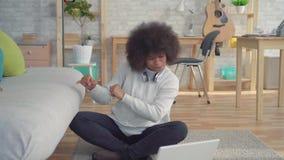 Schöne Afroamerikanerfrau mit einer Afrofrisur, die auf dem Boden mit einem Laptop gelernt über den Gewinn sitzt stock video