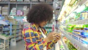 Schöne Afroamerikanerfrau mit einer Afrofrisur im Speicher wählt Jogurt stock video footage