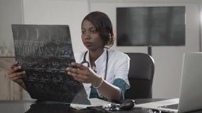 Schöne Afroamerikanergesundheitswesenarbeitskraft mit Röntgenstrahl, medizinisches internationales Konzept, schwarzes Doktordenke stockbild