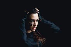 Schöne aggressive Frau über dunklem Hintergrund Dunkel und mysteriös steht ein hübsches Mädchen im Schatten mit camoflauge Farbe lizenzfreie stockfotos