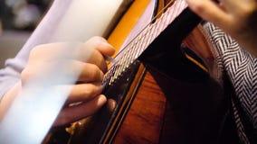 Schöne Akustikgitarre der Nahaufnahme, die von der Frau sich hinsetzt, Musikerkonzept gespielt wird Frau, welche die Gitarrennaha lizenzfreie stockbilder