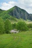 Schöne alpine Landschaft mit einer hohen Klippe und einem Fluss Stockfotos