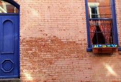 Schöne alte Backsteinmauer mit blauer Tür und Fenster Stockfotos