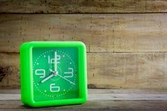 Schöne alte grüne Uhr auf hölzernem Hintergrund Lizenzfreie Stockfotografie