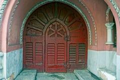 Schöne alte rote Holztür auf der Wand des Hauses Lizenzfreie Stockfotografie