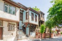 Schöne alte Straße herein in die Stadt mit Häusern mit hölzernem Fensterladen Lizenzfreie Stockfotografie