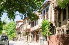 Schöne alte Straße herein in die Stadt mit Häusern mit hölzernem Fensterladen Lizenzfreies Stockbild