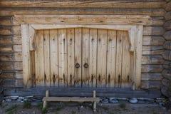 Schöne alte Tür auf der hölzernen Wand des alten Hauses Ausgezeichneter Hintergrund Stockbild