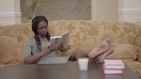 Schöne amerikanische afrikanische Frau, die im Wohnzimmer auf dem Trainer sitzt und interessantes Buch liest stock footage