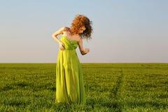 Schöne angeredete Frau mit einem Kleid des langen Grüns auf Feldern lizenzfreie stockfotografie