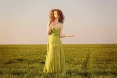 Schöne angeredete Frau mit einem Kleid des langen Grüns auf Feldern lizenzfreie stockbilder