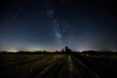 Schöne Ansicht der Milchstraße über einem bebauten Feld und entfernt Lizenzfreie Stockfotos