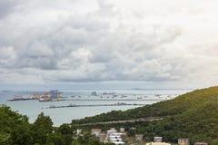 Schöne Ansicht des Öltanks nahe Gebirgs- und Hafenschiffsyard und der Brücke mit Arbeitskran für Import-export im Meer unter Dämm lizenzfreie stockfotos