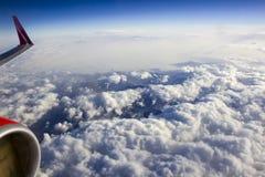 Schöne Ansicht des Himmels von der Öffnung, der Maschine und des Flügels, Wolken während des Fluges Lizenzfreies Stockfoto