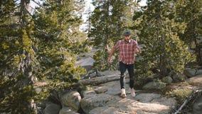 Schöne Ansicht des jungen hübschen glücklichen Mannes, der unten auf große Felsen beim an der Yosemite-Parkzeitlupe allein wander stock video footage