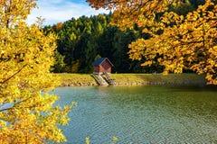 Schöne Ansicht des kleinen Holzhauses auf Bank von See nahe Wald während des Herbstes lizenzfreie stockfotografie