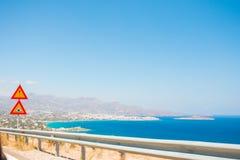Schöne Ansicht des Meeres vom Autofenster Verkehrsschilder und Zäune auf der Straße lizenzfreie stockbilder