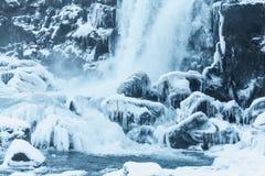 schöne Ansicht des szenischen Wasserfalls, des gefrorenen Flusses und der schneebedeckten Felsen in thingvellir Staatsangehörigem lizenzfreies stockbild