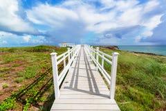 schöne Ansicht eines Gazeboweges, der in Richtung zum Strand und zum Ozean gegen magischen Hintergrund des blauen Himmels auf Kub lizenzfreie stockfotos