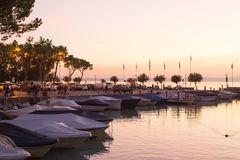 Schöne Ansicht mit Sonnenuntergangbooten und Garda See, Italien Lizenzfreies Stockfoto