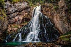 Schöne Ansicht von berühmtem Gollinger Wasserfall mit moosigen Felsen und grünen Bäumen lizenzfreie stockfotografie